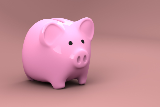 Pink plastic piggy bank used for storing and saving money sits against a darker pink background