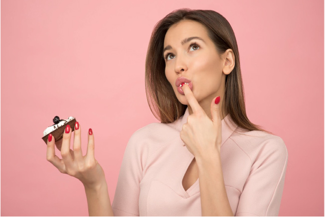 woman tasting a sugary treat thinking about tooth decay