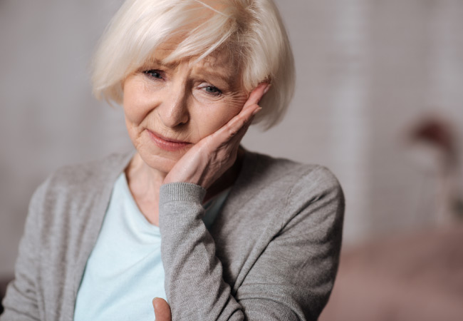 older woman holding her jaw in pain from tmj dysfunction