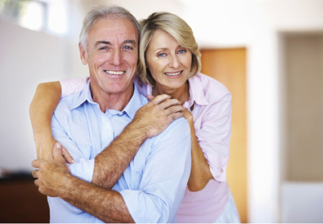 senior couple hug and smile after learning about dental crown options