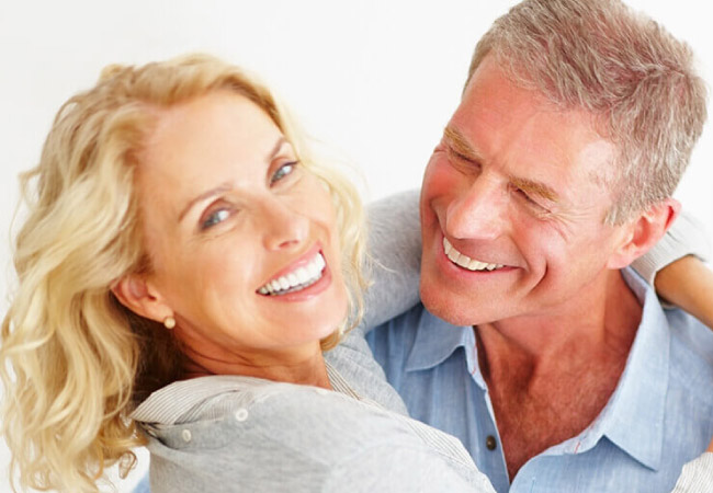 a coupe hug and smile after getting dental veneers